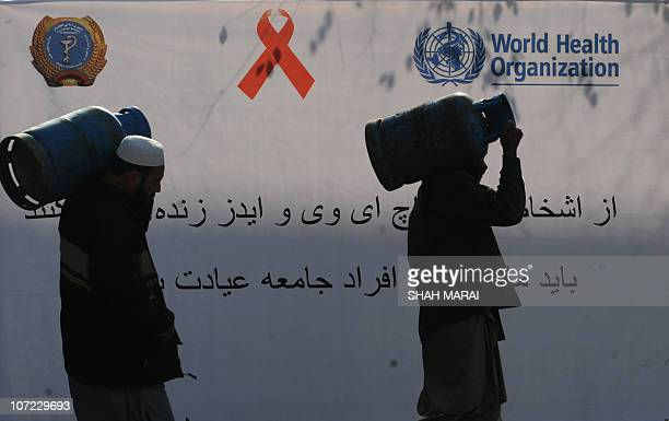 Afghan men carry gas cylinders in front of an HIV/AIDS awareness banner displayed outside the Ministry of Public Health in Kabul on World AIDS Day on...