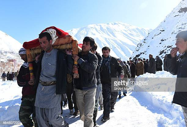 Afghan men carry the body of a victim of avalanches before funeral prayers in Khench district of Panjshir province north of Kabul on February 26 2015...