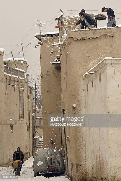 Afghan men clear the snow away from the roof of a house after snowfall in Kabul on February 6 2008 Several people have been killed in the southern...