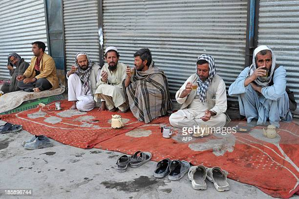 Afghan men drink tea and eat sugar bread in the early morning in Kabul on October 26 2013 Over a third of Afghans are living in abject poverty as...