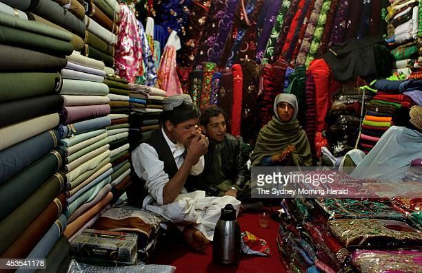 Afghan men drink tea in their fabric shop in Tarin Kowt Uruzgan Province Afghanistan January 24 2013