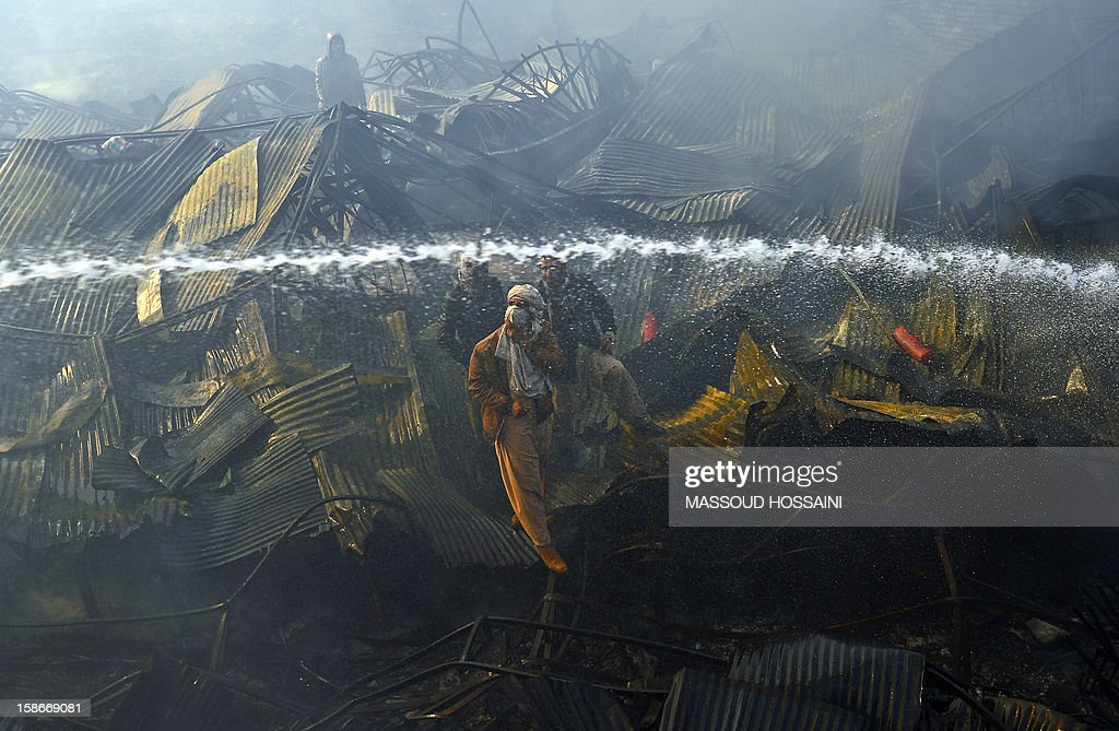 Afghan men guide firefighters after a huge fire swept through a market in Kabul on December 23, 2012. A huge fire swept through a market in downtown Kabul on December 23, destroying hundreds of shops and forcing the city's nearby money exchange to evacuate, police and witnesses said. There were no reports of any casualties in the early morning blaze which destroyed most of the cloth market's 500 shops, Kabul fire department officials told AFP. AFP PHOTO/ Massoud HOSSAINI