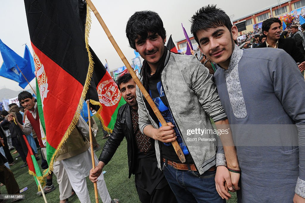 Afghan men hold national flags as Presidential Candidate Ashraf Ghani Ahmadzai holds a rally for thousands of supporters at the Ghazi stadium on April 1, 2014 in Kabul, Afghanistan. Mr. Ghani is a frontrunner in the April 5 vote to succeed President Hamid Karzai, in an election that is seen as a test of stability that will ensure continued Western donor aid for a nation torn by a Taliban insurgency. The Ghazi stadium is known as the site of amputations and executions during Taliban rule in the late 1990s.
