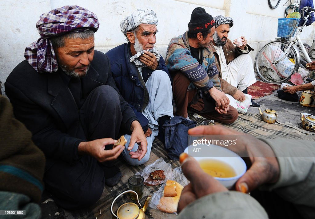 Afghan men labourers sit on the ground to drink tea in Mazar-i-Sharif in Balkh province on December 22, 2012. Once known as the 'mother of cities,' the ancient city of Balkh was a popular destination along the ancient Silk Route. Balkh was destroyed by Mongol conqueror Genghis Khan during his rule, with the city's ruins remaining as a tourist attraction today. AFP PHOTO/ Qais Usyan
