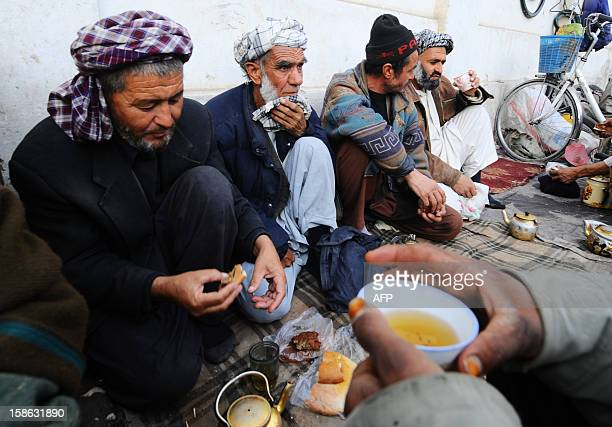 Afghan men labourers sit on the ground to drink tea in MazariSharif in Balkh province on December 22 2012 Once known as the 'mother of cities' the...