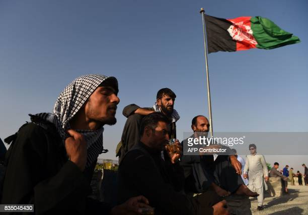 Afghan men look on as they drink tea near at the top of the Wazir Akbar Khan hilltop in Kabul on August 18 ahead of Afghan Independence Day Afghan...
