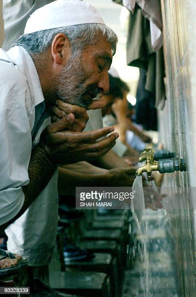 Afghan men perform ritual ablutions before offering Friday namazprayers at the PuleKhshti mosque in Kabul16 September 2005 ahead of forthcoming key...