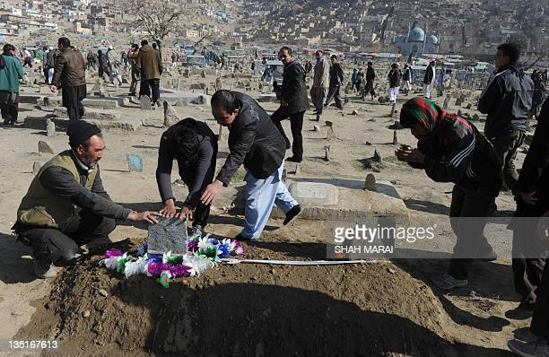 Afghan men pray over the grave of a victim of a bomb attack against Shiite Muslims at the KartE Sakhi cemetery in Kabul on December 7 2011 Afghans...