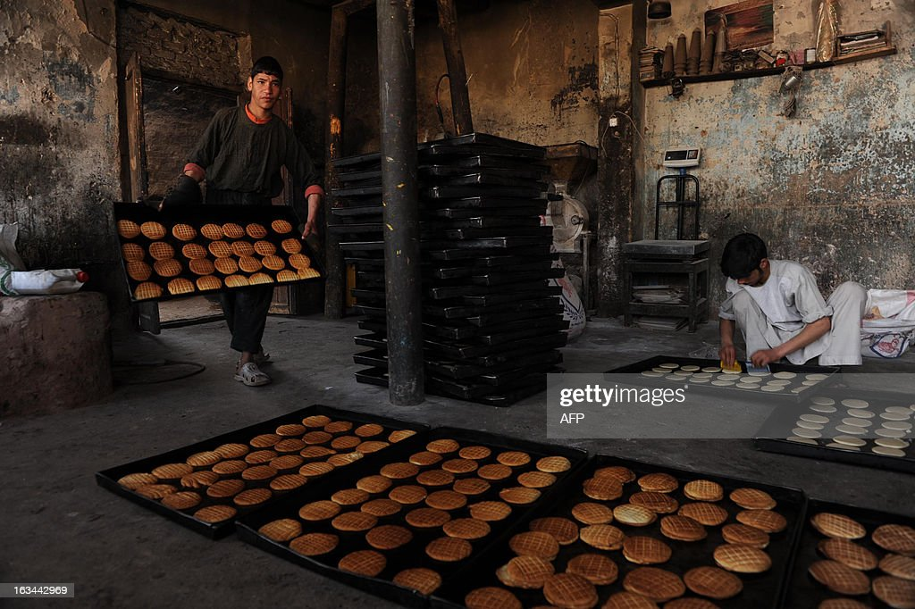 Afghan men prepare cookies at a traditional cookie factory in Herat on March 9, 2013. Afghanistan is having trouble keeping hard-earned development gains due to looming security challenges when NATO military forces withdraw in 2014, an internal World Bank audit said. AFP PHOTO/Aref KARIMI