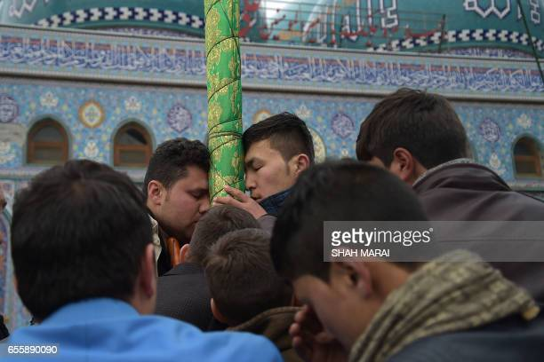 Afghan men reach the holy mace to kiss it in front of the Sakhi shrine during Nowruz festivities which mark the Afghan New Year in Kabul on March 21...