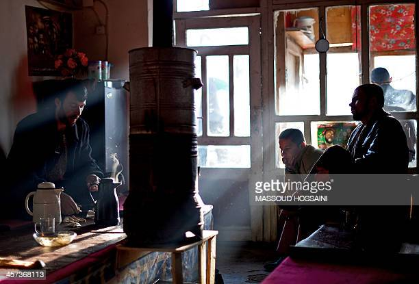 Afghan men sit and drink tea in a tea house in Mahmud Raqi capital of Kapisa province on December 17 2013 Even with sustained growth of six percent a...