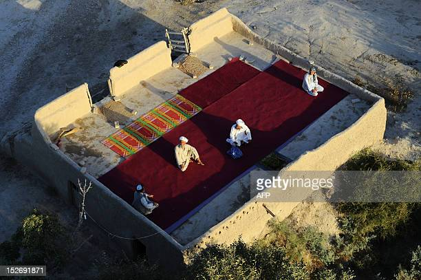 Afghan men sit atop an open mosque in Zadyan district of Balkh province on September 23 2012 AFP PHOTO/QAIS USYAN