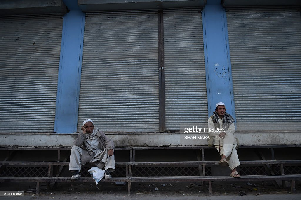 Afghan men sit outside shuttered shops as they wait for Iftar, the time to break fast during the Islamic month of Ramadan, in Kabul on June 28, 2016. Throughout the month, devout Muslims must abstain from food, drink and sex from dawn until sunset when they break the fast with the Iftar meal. / AFP / SHAH