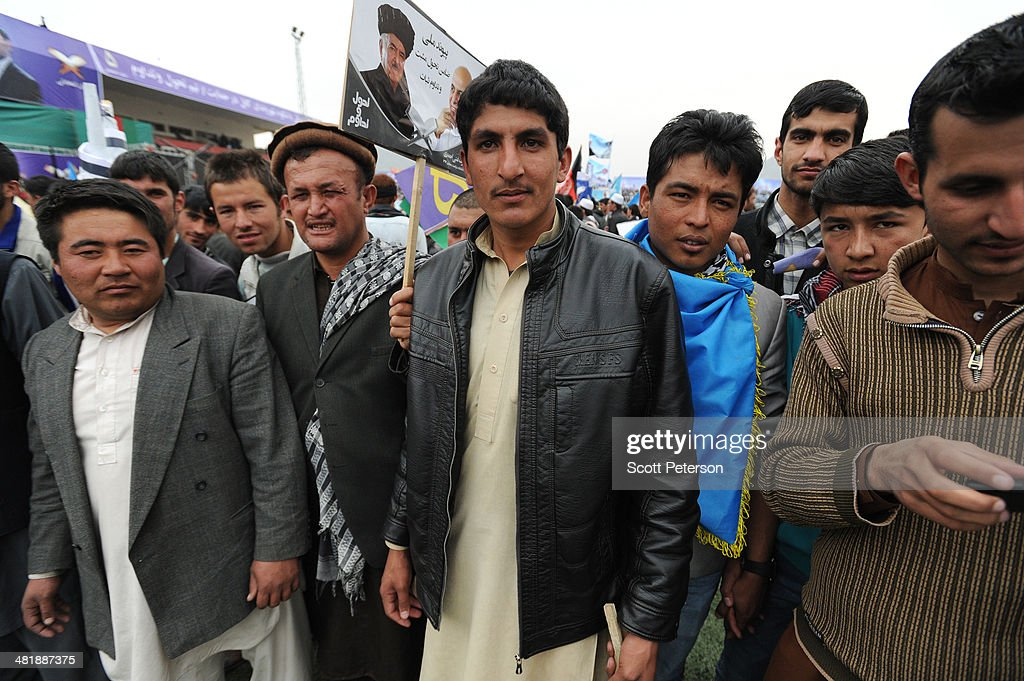 Afghan men stand with a campaign sign as Presidential Candidate Ashraf Ghani Ahmadzai holds a rally for thousands of supporters at the Ghazi stadium on April 1, 2014 in Kabul, Afghanistan. Mr. Ghani is a frontrunner in the April 5 vote to succeed President Hamid Karzai, in an election that is seen as a test of stability that will ensure continued Western donor aid for a nation torn by a Taliban insurgency. The Ghazi stadium is known as the site of amputations and executions during Taliban rule in the late 1990s.