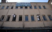 Afghan men take photographs with their smartphones from a window of a building during an antigovernment demonstration in the city of Kabul on July 23...