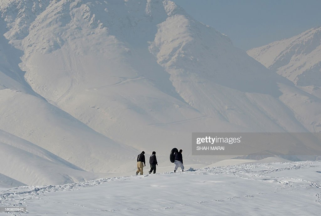 Afghan men walk on a snow covered mountain on a cold winter's day outside Kabul on February 7 , 2013. Despite massive injections of foreign aid since the fall of the Taliban in 2001, Afghanistan remains desperately poor with the lowest standards in the world. AFP PHOTO/ SHAH Marai