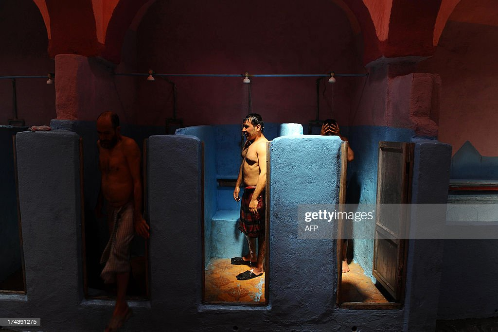 Afghan men wash at a traditional hamam bathhouse in Herat on July 25, 2013. Afghans usually come in the morning for one-hour sessions inside the steam-filled rooms, paying 50 Afghanis (1 USD) each. AFP PHOTO/ Aref Karimi