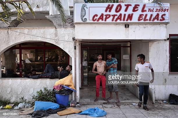 Afghan migrants stand on August 16 2015 outside the abandoned Captain Elias hotel on the Greek Aegean island of Kos where migrants arriving to the...
