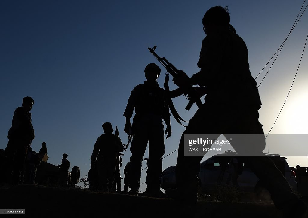 Afghan military personnel walk near the airport during fighting between Taliban militants and Afghan security forces in Kunduz on October 1 2015...