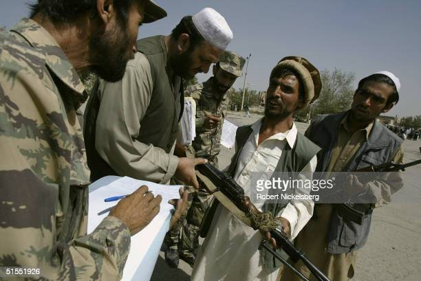 Afghan militia men and former mujahideen loyal to current Defence Minister Marshal Fahim turn in their mostly Sovietera weapons under a United...