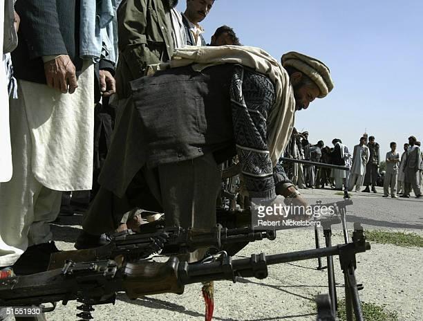 Afghan militia men and former mujahideen loyal to current Defense Minister Marshal Fahim turn in their Sovietera weapons under a United Nations...