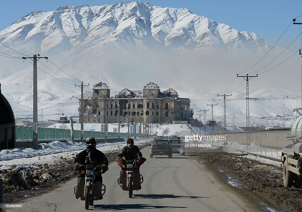 Afghan motor-cyclists ride in front of the war-damaged Darlaman Palace in Kabul on February 7, 2013. Despite massive injections of foreign aid since the fall of the Taliban in 2001, Afghanistan remains desperately poor with the lowest standards in the world. AFP PHOTO/ SHAH Marai