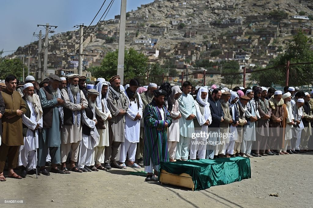 Afghan mourners offer funeral prayers for slain police cadet Mohinddin at The Qul Ab Chakan cemetery in Kabul on July 1, 2016, after his death in a Taliban attack in the Afghan capital. Mohinddin, who loved football and was passionate about joining the Afghan police force, was to return home after his graduation as a cadet to celebrate Eid al-Fitr with his family. He was one of 32 young cadets mown down by the Taliban one day before, killed in a suicide attack on the edge of the Afghan capital hours after their graduation. / AFP / WAKIL