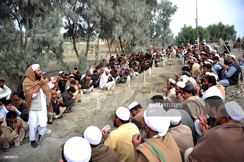 Afghan mourners offer prayers next to the graves of young girls at a cemetery in Jalalabad on December 17, 2012, after their deaths following the explosion of a landmine while they were collecting firewood. Ten young girls were killed when a landmine exploded while they were collecting firewood in eastern Afghanistan's Nangarhar province, officials said. The girls, aged between nine and 11, died when one of them accidentally struck the mine with an axe, Chaparhar district governor Mohammad Sediq Dawlatzai told AFP. AFP PHOTO/ Noorullah Shirzada