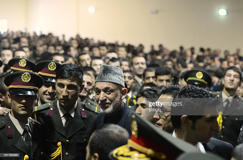 Afghan National Army officrs pose for pictures with Afghan President Hamir Karzai (C) during a conference at the National Miltary Academy in Kabul on February 16, 2013. Afghanistan has committed to taking full responsibility for its own security after US forces leave, and the White House said Afghan security forces now count 352,000 troops, thanks to a broad NATO training effort.