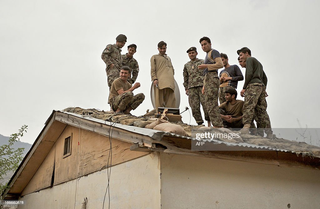 Afghan National Army (ANA) soldiers of the Kandak 6 watch a cricket telecast, broadcast from a satellite receiver, from the roof of their barracks at forward base Honaker Miracle in Watahpur District in Kunar province on April 15, 2013. Budget cuts and war fatigue in Western capitals mean the 100,000 soldiers left serving in NATO's International Security Assistance Force are packing up and taking off as the mission prepares to close next year. AFP PHOTO/Manjunath KIRAN