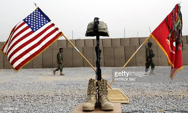 Afghan National Army soldiers pass the boots gun helmet and dogtags of US army First Lieutenant Todd W Weaver displayed in his honor at Combat...