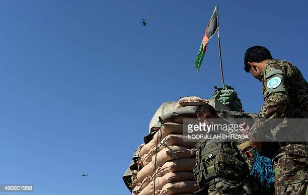 Afghan National Army soldiers stand guard as a US helicopter flies over Jalalabad Airport where a US C130 military transport plane crashed in...