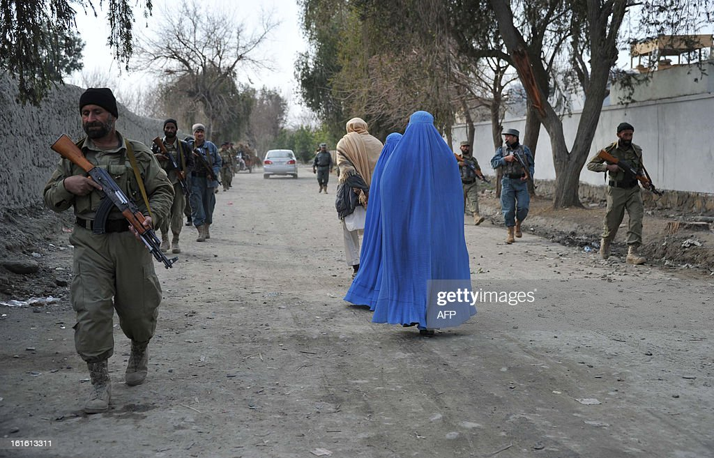 Afghan National Police (ANP) and Local Police (ALP) personnel walk past a family during a patrol in Koz Kunar district Nangarhar province on February 13, 2013. The Afghan government welcomed President Barack Obama's announcement that the United States will withdraw 34,000 troops from the war-torn country over the next year. NATO, which has about 37,000 troops in Afghanistan, will also withdraw them in stages before the end of 2014. AFP PHOTO/ Noorullah Shirzada