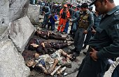 Afghan National police personnel stand over the bodies of Taliban militants after an attack on the Afghan parliament building in Kabul on June 22...