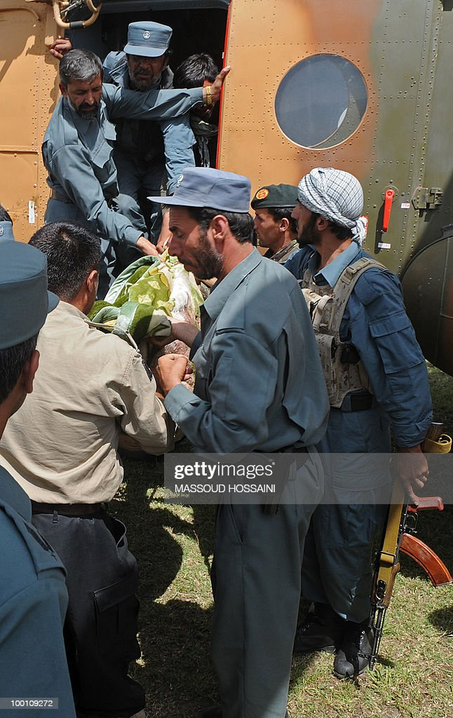 Afghan National Police (ANP) personnel take out a dead body from an Afghan military helicoopter in Charikar city of Parwan province, north of capital Kabul on May 21, 2010. Bodies and wreckage of an Afghan passenger plane that crashed with 43 people on board have been found on a mountainside with no immediate sign of any survivors, a government minister said. The ageing Pamir Airways plane was carrying three Britons, an American and dozens of Afghans when it came down during bad weather on May 17 during a scheduled flight from the northern province of Kunduz to Kabul. AFP PHOTO/Massoud HOSSAINI