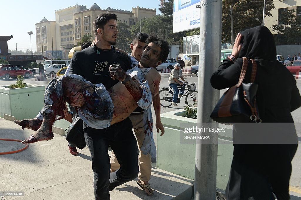 Afghan national rugby team captain Sayed Mustafa Sadat runs with a victim of a suicide attack in his arms to a hospital in Kabul on September 16 2014...