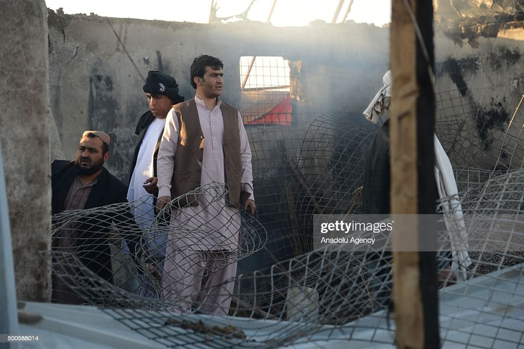 Afghan officials inspect a building at an airfield following the attack of Taliban militants in Kandahar Afghanistan on December 09 2015 At least 46...