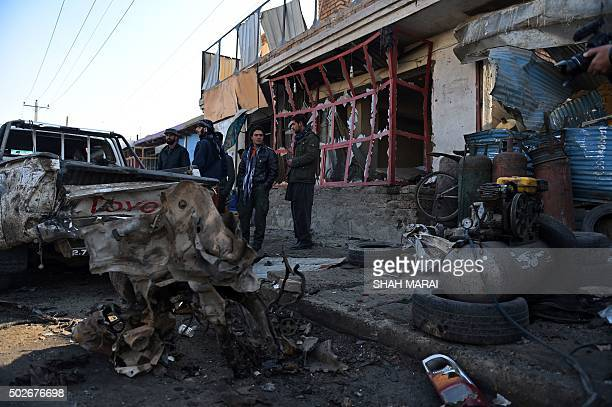 Afghan onlookers stand at the site of a suicide car bomb near the international airport in Kabul on December 28 2015 A Taliban bomber has detonated...