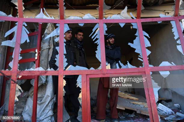 TOPSHOT Afghan onlookers watch through the broken windows of a bakery at the site of a suicide car bomb near the international airport in Kabul on...