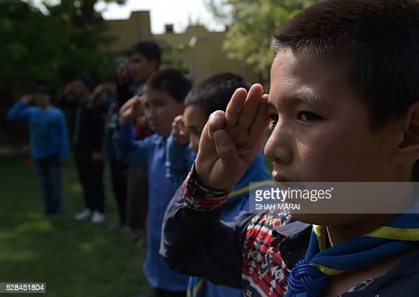 Afghan orphans salute before taking part in a quiz at the Physiotherapy and Rehabilitative Support for Afghanistan NGO which supports vulnerable...