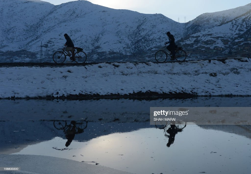 Afghan pedestrians bike along the Shuhada lake at sunset in Kabul on December 31, 2012. Over a third of Afghans are living in abject poverty, as those in power are more concerned about addressing their vested interests rather than the basic needs of the population, a UN report said. AFP PHOTO/ SHAH Marai