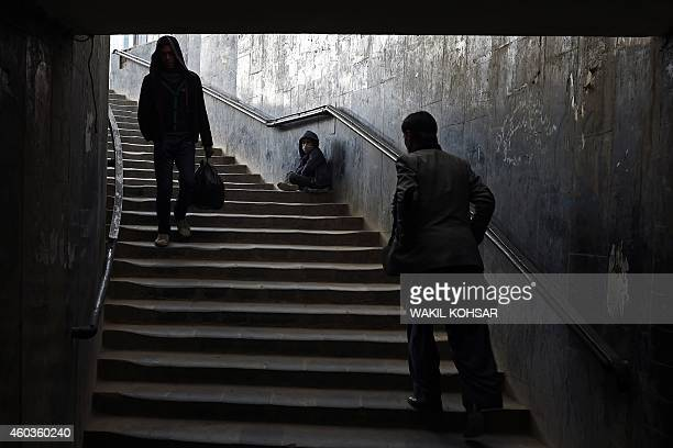 Afghan pedestrians walk past as a young boy beggar asks for alms in Kabul on December 12 2014 Afghanistan's economy has improved significantly since...