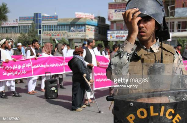 Afghan people and activists hold banners as Afghan security forces stand guard during a protest against Myanmar's oppression towards Rohingya Muslims...