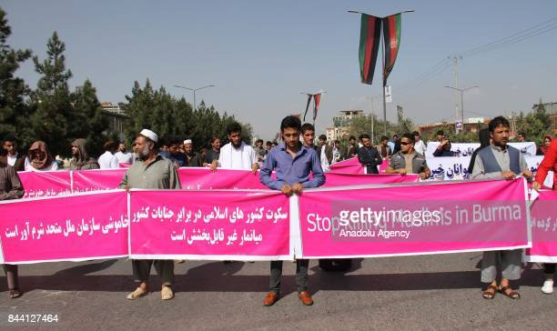 Afghan people and activists hold banners during a protest against Myanmar's oppression towards Rohingya Muslims in front of the United Nations'...