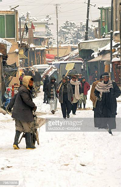 Afghan people go about their business on a snow covered street in Kabul on February 6 2008 Several people have been killed in the southern Afghan...