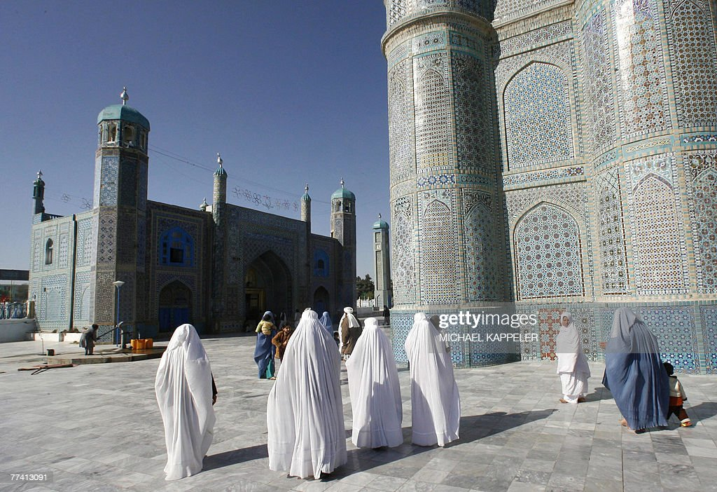 Afghan people walk in front of the of the shrine of Hazrat-i-Ali, also called the Blue Mosque, in Mazar-i-Sharif, the capital of Balkh province, north of Kabul, 05 April 2007. The Hazrat-i-Ali shrine, the main architectural element in Mazar-i-Sharif, was covered with earth to escape the ravage of Genghis Khan in 1220 and remained lost until it was uncovered during the rebuilding work in 1480s.