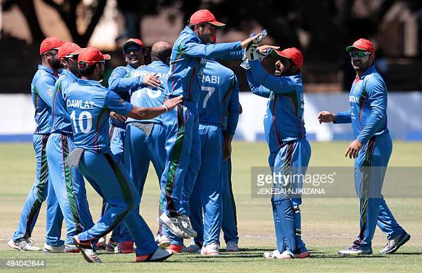 Afghan players celebrate a wicket during the final game in a series of five ODI cricket matches between Afghanistan and hosts Zimbabwe at Queens...