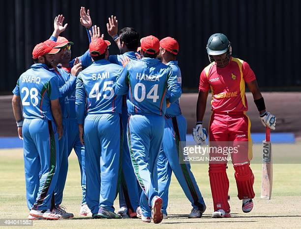 Afghan players celebrate next to Zimbabwe's Chamunorwa Chibhabha during the final game in a series of five ODI cricket matches between Afghanistan...
