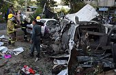 Afghan police and security forces stand next to a body as they inspect the site of a car bomb in Kabul on August 22 2015 A suicide car bomb...