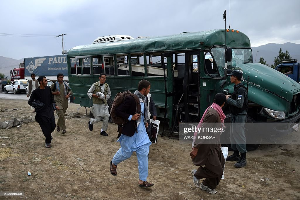 Afghan police cadets run past the wreckage of a bus on the outskirts of Kabul on June 30, 2016, after a suicide bomb attack that targeted a convoy of buses transporting police cadets. At least 27 policemen were killed and 40 wounded after a bomb attack claimed by the Taliban struck a convoy of buses transporting police cadets in Kabul, the interior ministry said. / AFP / WAKIL